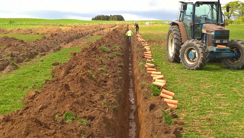 installing clay draining pipes in a deep trench in a field